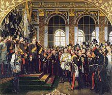 Tableau d'Anton von Werner: proclamation de l'empire allemand par l'empereur Guillaume Ier le 18 janvier 1871 avec Bismarck (en uniforme blanc) dans la galerie des glaces du château de Versailles. Bismarck est au pieds des marches menant à l'empereur, les deux hommes sont entourés d'une foule nombreuse.