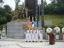 A line of sailors in white dress naval uniforms in front of a large monument while another soldier in green stands at a podium beside