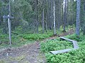 Bänk vid en skylt som visar riktning för vandringsled.jpg