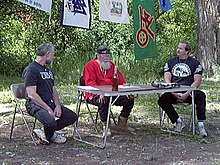 Three middle-aged white men sit at a camping table outdoors.
