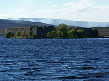 In the foreground are the blue waters of a lake. Beyond that is a wooded shoreline on which there are the ruins of a large walled structure. Smoke drifts across the moorland in the distance.