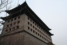A tall rectangular stone building with a Chinese-style roof seen from near its base with some bare tree branches in front