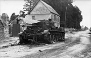 A knocked out tank sits at the side of a road, in front of a two story house.