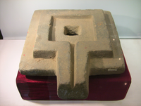 Photograph of a large stone yoni in a museum display case