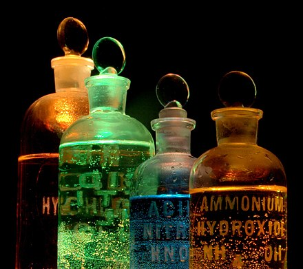 Solutions of substances in reagent bottles, including ammonium hydroxide and nitric acid, illuminated in different colors Chemicals in flasks.jpg