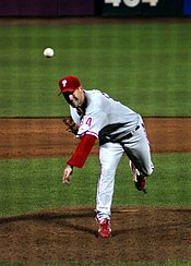 A man in a gray baseball uniform with red sleeves and cap throws a baseball with his left arm.