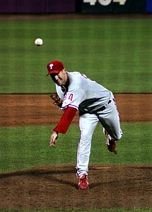 A left-handed man in a gray baseball uniform with red trim and a red baseball cap stands on a pitchers' mound having thrown a baseball toward the camera.