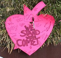 "Heart-shaped sign reading ""We stand with Comet"""