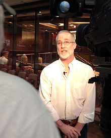 David Nelson speaking with a television-news reporter outside the Salt Lake County Council Chambers at the county adoption of a joint commemorative resolution in 2012