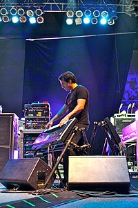 Derek Sherinian on stage playing a keyboard mounted on an angled keyboard stand. In the background are amplifiers, effects racks, a guitar rack and stage lighting mounted on the roof.