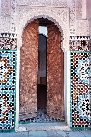 Ben Youssef Madrasa - A small doorway in Ben Youssef Madrasa, Marrakech. The wooden doors are carved with a girih pattern of strapwork. The arch is surrounded with arabesques; to either side is a band of Islamic calligraphy, above colourful geometric zellige tilework.