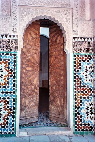 Islamic geometric patterns - A doorway in Ben Youssef Madrasa, Marrakech. The wooden doors are carved with a girih pattern of strapwork with a 16-point star. The arch is surrounded with arabesques; to either side is a band of Islamic calligraphy, above colourful geometric zellige tilework with 8-point stars.