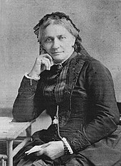 Retouched black-and-white photograph of an older woman, sitting next to a table on which she leans her right arm, with the hand supporting her head while her left hand holds a paper in her lap, dressed in black and with black lace covering most of her whitish hair