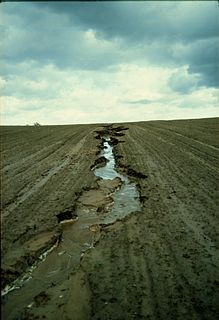 Soil erosion washing or blowing away of the top layer of soil