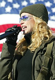 A blonde woman wearing a woolly hat and glasses singing into a microphone in front of the American flag