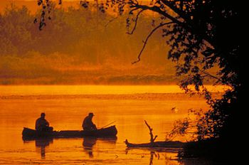 English: Fisherman in a canoe at sunset