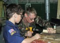 Flickr - Official U.S. Navy Imagery - Seabee helps boy scout build a derby car..jpg
