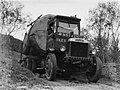 Front on view of a Leyland truck transporting a piece of Kauri along a dirt road (AM 75776-1).jpg
