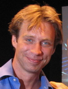 Color photograph of a middle-aged, blond-haired man posing for the camera.