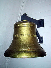 "A large brass bell, engraved with the words ""S.M.S. Von Der Tann"", suspended on a white brick wall."