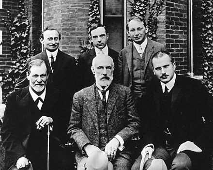 Group photo 1909 in front of Clark University. Front row: Sigmund Freud, G. Stanley Hall, Carl Jung; back row: Abraham A. Brill, Ernest Jones, Sandor Ferenczi. Hall Freud Jung in front of Clark 1909.jpg