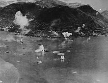 Aerial photo of an island with an urban area along its shore and a steep mountain in the center. A large number of ships are in the water next to the island, and plumes of water are erupting near some of them.