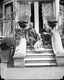 Howard Sturgis and William Haynes Smith on the steps with two dogs at Queen's Acres, Windsor, before 1920.jpg