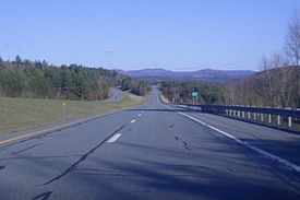 A four lane highway in the woods looking towards mountains on a sunny day.
