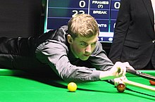 Picture of James Cahill playing snooker.