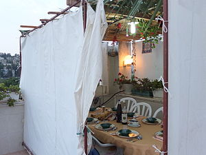 Sukkah - Canvas-sided sukkah on a roof, topped with palm branches and bamboo s'chach