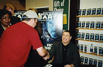 Battlefield Earth (film) - John Travolta signing copies of the book Battlefield Earth during a promotional tour in 2000