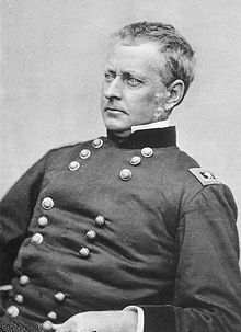 Historic photograph of the head and torso of a man in American Civil War uniform. He appears to be seated and is looking off to the right, he is clean shaven, with short gray hair. His expression is stern.