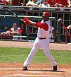 "A man in a white baseball uniform with red sleeves and a red batting helmet with a white ""C"" on it watches the ball travel following his swing."