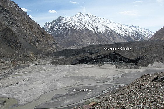 Khurdopin glacier and Shimshal River, Gilgit-Baltistan, northern Pakistan 2017. Several glaciers flow into the Shimshal Valley, and are prone to blocking the river. Khurdopin glacier surged in 2016-17, creating a sizable lake. Khurdopin glacier & Shimshal River.jpg