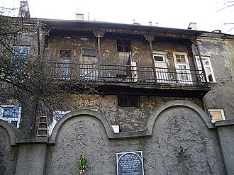 Kraków Ghetto - One of two preserved segments of Ghetto wall, with a memorial plaque and typical ghetto home in the background