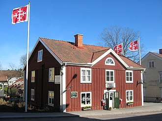 Kisa, Sweden - Café Columbia with its emigration museum is right on national road 34, passing through the small town. Kinda municipality's coat of arms is seen on the flags.