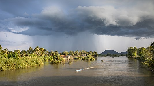 Landscape with stormy clouds and a pirogue on the Mekong at golden hour in Si Phan Don