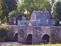 stone gatehouse and gateway seen beyond three arches of old bridge over river