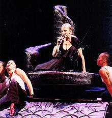 Madonna in a black dress atop a sloping structure, with her dancers below.