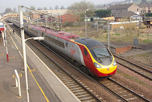 Lockerbie railway station - A Virgin Pendolino accelerates with a Glasgow Central - London Euston service