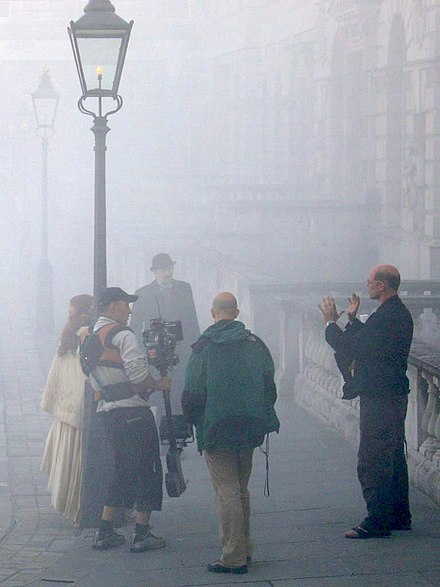 The film director, on the right, gives last minute direction to the cast and crew, while filming a costume drama on location in London. - Film director