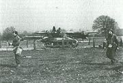 A Locust tank, facing right, on a road that cuts through a field. Several uniformed men move in the opposite direction in the foreground. A large military glider can be seen in the background, just behind the Locust.