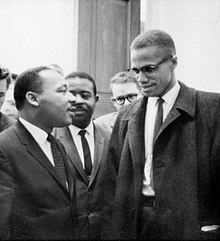 Malcolm X and Martin Luther King speak to each other thoughtfully as others look on