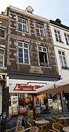 foto van Huis met lijstgevel in de trant der zgn. Maaslandse renaissance. Gevelsteen met leeuw en vijzel IN DE GOUDEN LEEUW, afkomstig van Spilstraat 5.