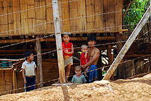 A man and four children stand in front of a wooden hut and behind a wire fence.