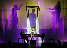 A blonde woman sits atop a piano and sings. A long, white cloth hangs around her while a silhouette behind the woman shows two male figures as if holding the white cloth.