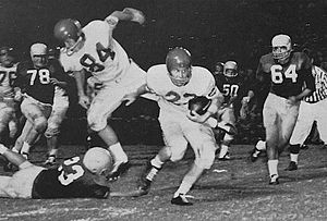 1957 Houston Cougars football team - Houston halfback Claude King advances against Miami in a rushing play, while end Bob Borah blocks