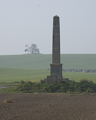 "Battle of Marston Moor - The monument commemorating the battle, alongside the Long Marston - Tockwith road. In the background is Marston Hill, crowned by the clump of trees known as ""Cromwell's plump"", reputedly the site of the Parliamentarian and Covenanter headquarters"