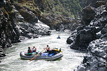 Two rafts, one with three people and one with one person, negotiate fast-moving water in a narrow, rocky river canyon.