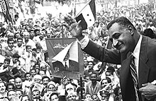 A man wearing a suit and tie with his upper body jutting out, waving his hand to crowds of people, many dressed in traditional clothing and holding posters of the man or three-striped, two-star flags
